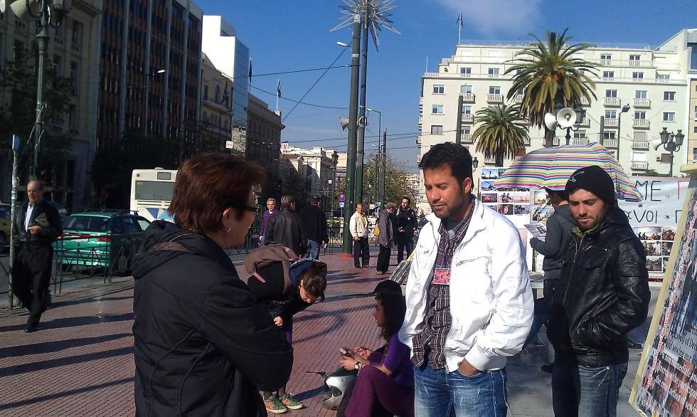 Greek woman stops to talk to Afghan asylum seeker