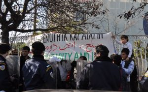 police look on as Afghan men defiant in Greece