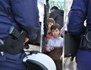 shot of police gun and afghan boy in athens Greece